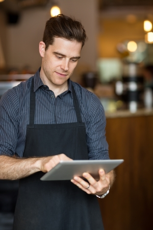 Young male owner using digital tablet while standing in shop photo