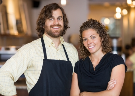 small business team: Portrait of happy male and female owners standing together in coffee shop