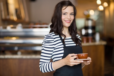 cafe shop: Portrait of beautiful waitress holding coffee cup while standing in cafeteria