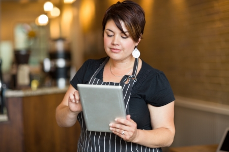 mandil: Hermosa propietario femenina que usa la tableta digital en el café