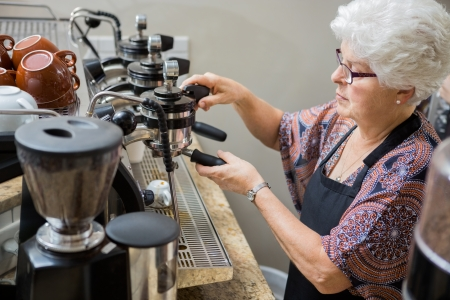 Senior female barista preparing coffee in cafe photo