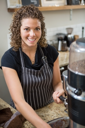 Portrait of happy barista preparing coffee in cafe photo