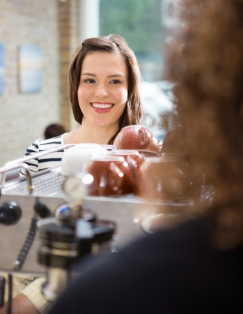 Beautiful customer looking at waitress in cafeteria photo