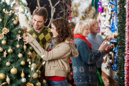 Happy young couple looking at Christmas tree with parents shopping in background at store photo