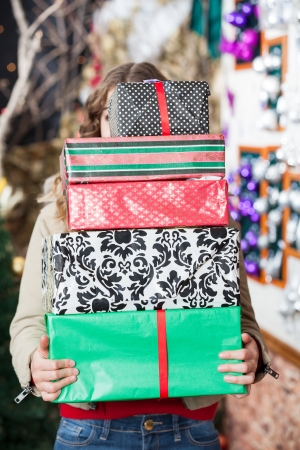 Young woman hiding behind stack of Christmas gifts in store Stock Photo - 23726189