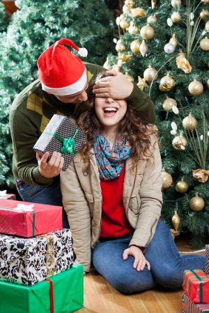 Young man in Santa hat surprising woman with Christmas gifts in store photo