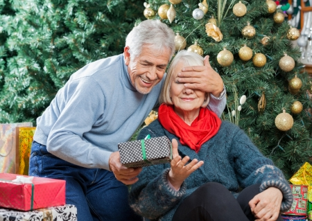 Senior man covering womans eyes while surprising her with Christmas gifts in store photo