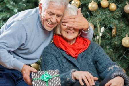 Happy senior man surprising woman with Christmas gift in store photo