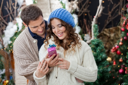 Happy young couple with Christmas present standing at store photo