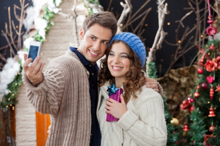Happy young couple taking selfportrait through cellphone in Christmas store photo