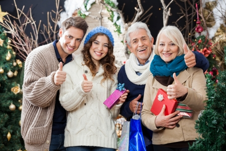Portrait of happy family with Christmas presents and shopping bags gesturing thumbs up in store photo