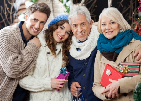 Portrait of happy loving family with Christmas presents and shopping bags standing in store photo
