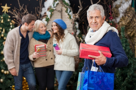 Portrait of happy senior man holding Christmas presents with family standing at store photo