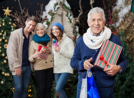 Portrait of cheerful man holding Christmas presents and shopping bags with family standing in background at store photo
