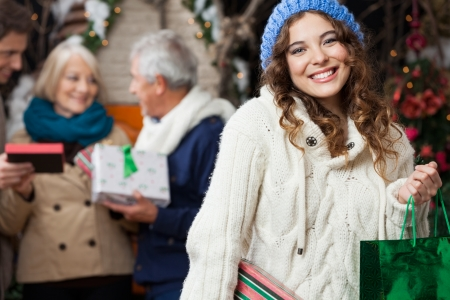 christmas shopping: Portrait of happy young woman holding in sweater with family standing at Christmas store Stock Photo