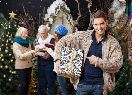 Portrait of happy young man pointing at Christmas present with family standing at store photo