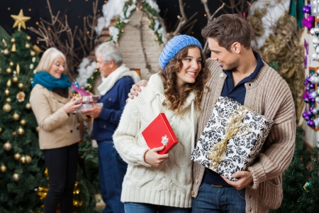 Happy young couple holding Christmas presents with parents standing in background at store photo