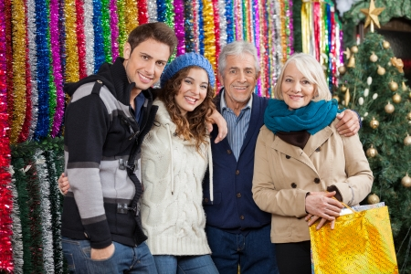 Portrait of happy family standing together against tinsels at Christmas store photo