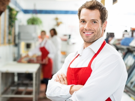 butcher shop: Portrait of happy male butcher standing arms crossed at store with working colleagues