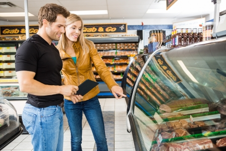 meat counter: Couple choosing meat from display cabinet at butchers shop Stock Photo