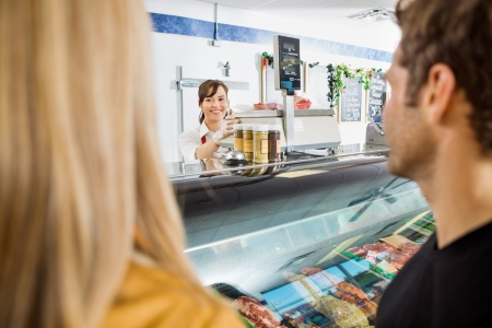 Beautiful saleswoman looking at customers while working in butchers shop photo