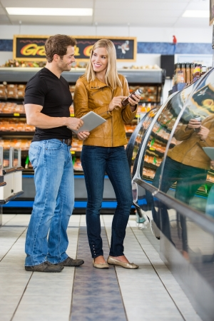 checking ingredients: Couple with digital tablet checking ingredients of product at butchers shop