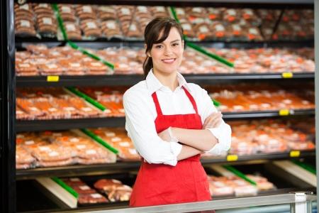 csemege: Portré szép elárusítónő állt keresztbe font karral a pult hentesüzlet Stock fotó