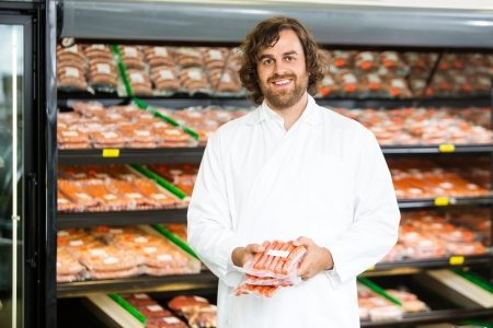 Portrait of happy salesman holding meat packages in butcher's shop photo