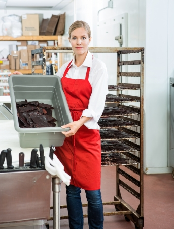 Portrait of female worker showing beef jerky in basket while standing at butcher's shop photo