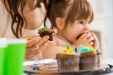 Cropped image of mother holding cupcake with girl eating cake at birthday party photo