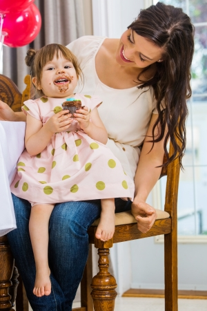 Portrait of birthday girl eating cupcake while sitting on mothers lap at home photo