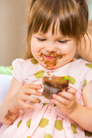 dirty faces: Happy girl eating birthday cake with icing on her face at home Stock Photo