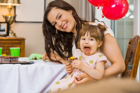 Portrait of happy mid adult woman with daughter eating birthday cake at home photo