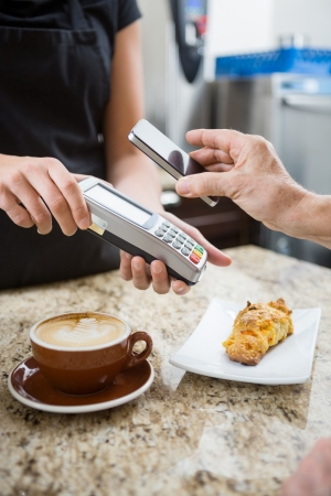 Customer paying for coffee using NFC technology photo