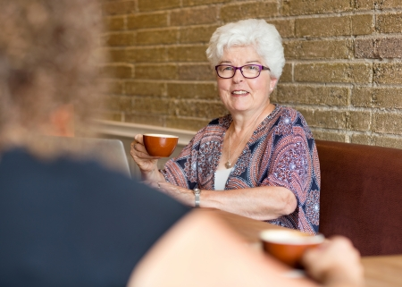Portrait of senior female customer having coffee in cafeteria photo
