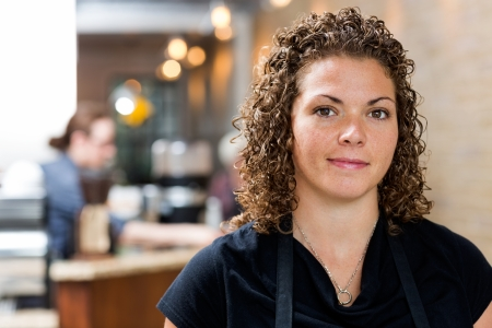 mid adult female: Portrait of confident mid adult female owner at cafe Stock Photo