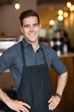 Portrait of happy male owner with hands on hips standing in cafe photo