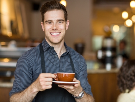 Portrait of happy waiter holding coffee cup while standing in cafeteria photo