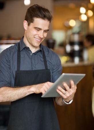 식당에서 디지털 태블릿에 남성 소유자 서핑 인터넷 미소