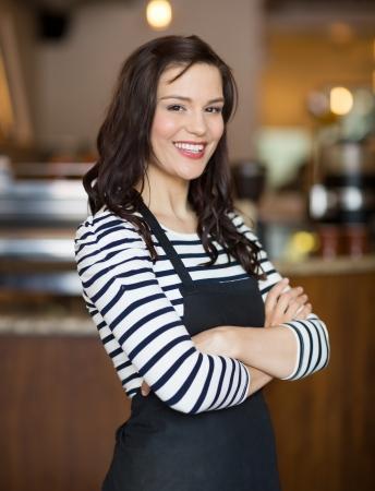 mandil: Retrato de camarera joven y feliz de pie brazos cruzados en el café