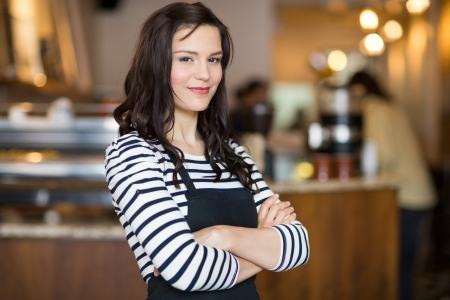 owners: Portrait of pretty young waitress standing arms crossed in cafeteria