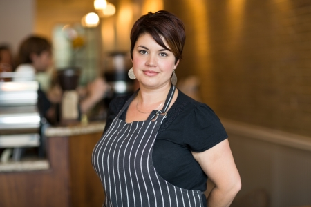 Portrait of confident young female owner smiling at cafeteria photo