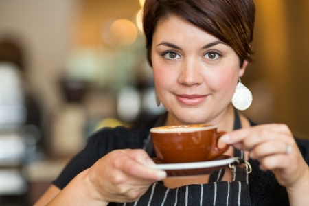 Portrait of beautiful waitress holding coffee cup in cafe photo
