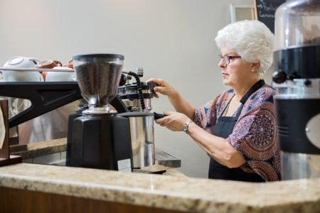 making coffee: Senior female barista making coffee in cafe Stock Photo