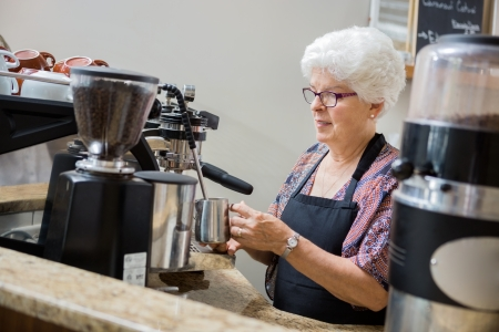 Senior waitress steaming milk for coffee in cafe photo