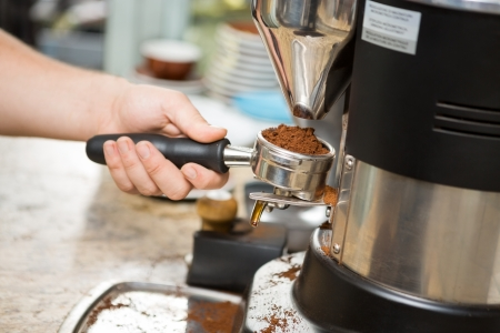 grinder machine: Cropped image of barista holding portafilter with ground coffee in cafe