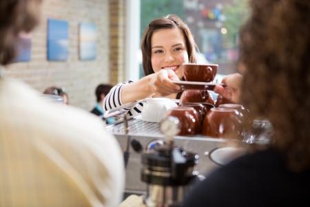 コーヒー ショップのバリスタのコーヒーを取る若い女性客