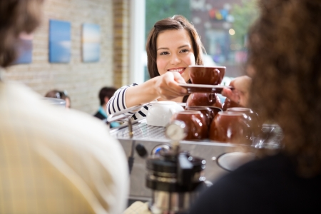 serving: Young female customer taking coffee from barista in coffee shop