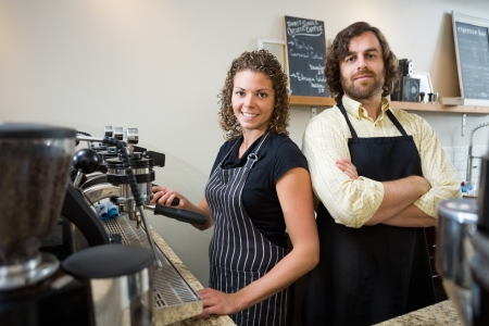 Portrait of confident workers standing at counter in coffeeshop photo