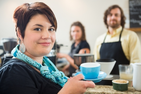 Portrait of beautiful woman holding coffee cup with owners in background in coffee shop photo